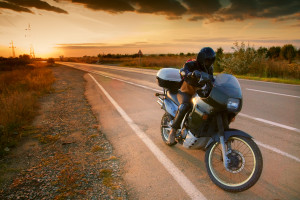 Biker and motorcycle on the road at sunset