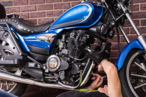 Lying Man Repairing Some Parts of his Motorbike